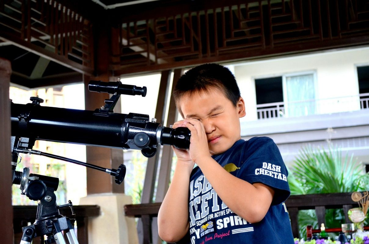 kid looking into a telescope