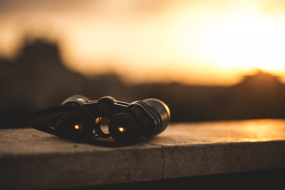 binoculars on a wall in the sunset