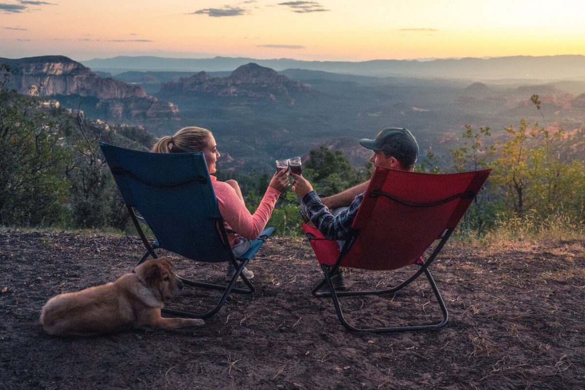 two people on camping folding chairs watching the sunset